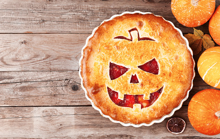 Delicious homemade pie for halloween with a filling of pumpkin-strawberry jam and peaches Stock Photo - 85386842