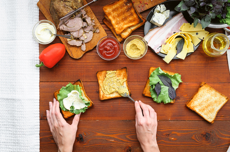 the hostess prepares a sandwich on a wooden table for guests Stock Photo