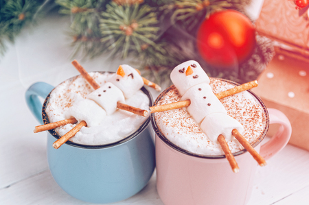 een mok met warme chocolademelk op een houten tafel met een marshmallow man die rust in een mok Stockfoto