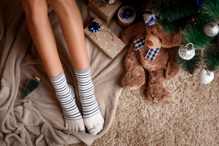 long-legged girl near the Christmas tree with gifts