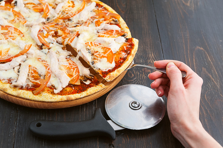 fresh and delicious Italian pizza on a wooden table and a pizza knife