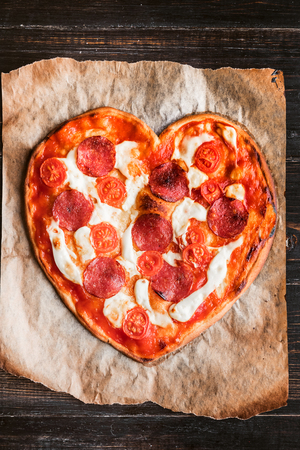 pizza in the shape of heart. lying on a paper for a baking and wood table made of ebony Stock Photo