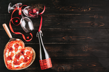 a festive dinner of pizza in the shape of a heart and a bottle of wine. Stock Photo - 92685110