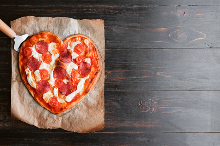 pizza in the shape of heart. lying on a paper for a baking and wood table made of ebony Standard-Bild