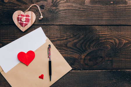 blank white sheet in an envelope on a wooden table, next to it is a ballpoint pen. declaration of love on St. Valentines Day