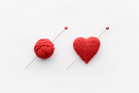 a knitted heart of red thread with an inserted knitting needle on a white background. and a hank of a red knitting thread