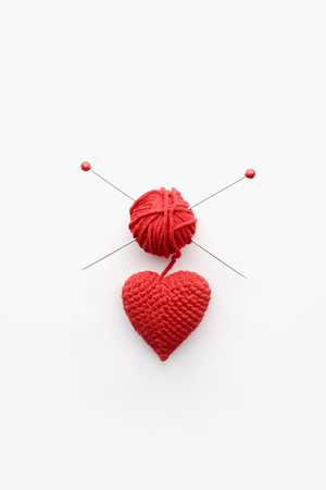 a knitted heart of red thread with an inserted knitting needle on a white background. and a hank of a red knitting thread Reklamní fotografie - 92788346