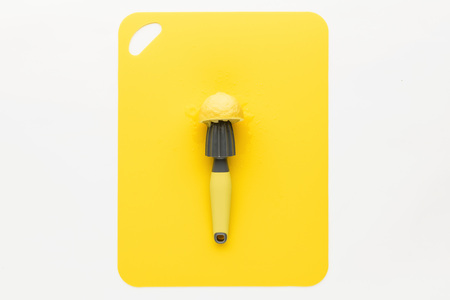 press for lemon with lemon on a yellow background