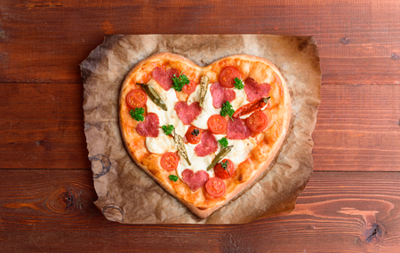the chef makes a pizza heart for the Valentines Day holiday. classic Italian pizza with salami and mozzarella 版權商用圖片