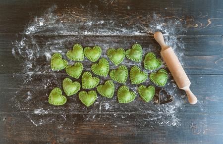 나무 표면에 심장 모양의 녹색 라비올리 스톡 콘텐츠