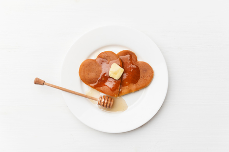 심장 모양의 빛 배경에 팬케이크. 발렌타인 데이를위한 축제 아침 식사의 개념 또는 사랑하는 사람을위한 즐거운 놀라움