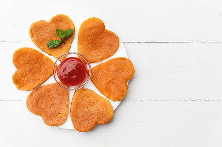 heart shaped pancakes on a light background. the concept of a festive breakfast for Valentines Day or a pleasant surprise for a loved one
