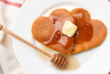 heart shaped pancakes on a light background. the concept of a festive breakfast for Valentine's Day or a pleasant surprise for a loved one Stock Photo