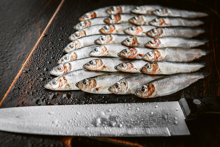 fresh raw fish anchovy and sprat on a wooden surface with a cutting knife Standard-Bild