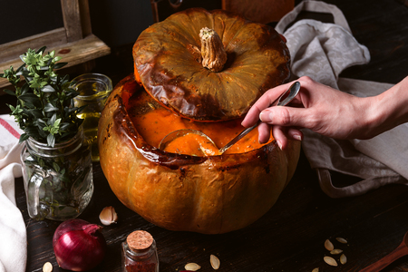 pumpkin cream soup poured into a baked pumpkin. still life in a rustic style. pumpkin seeds and spices next to the table.