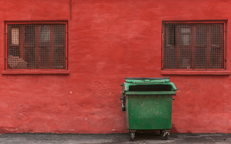 green garbage container on a red wall background