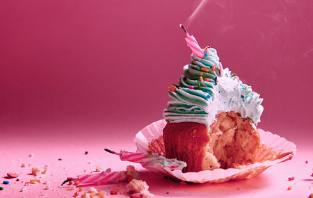 bitten muffin with cream with extinguished candles Stock Photo