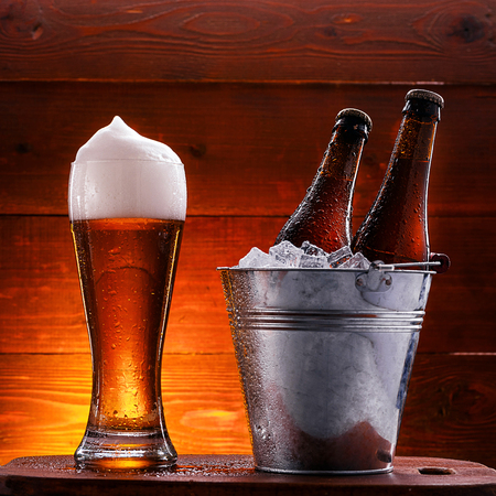 two bottles of beer in a bucket with ice and a glass of beer with lush foam next to a dark background