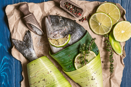two fresh raw dorado fish, wrapped in palm leaves, sprinkled with a mixture of peppers and large gimolais salt, with slices of lime and lemon, ready to be baked. cooking dinner concept for two