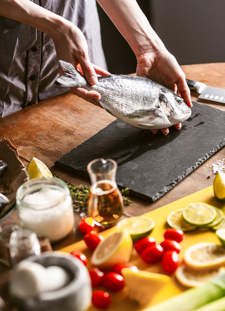 woman chef preparing fresh raw dorado fish