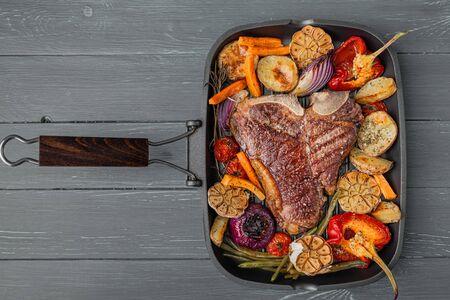 骨头上的嫩和多汁的牛排烧烤烤,烤蔬菜,鲜美和健康营养的概念