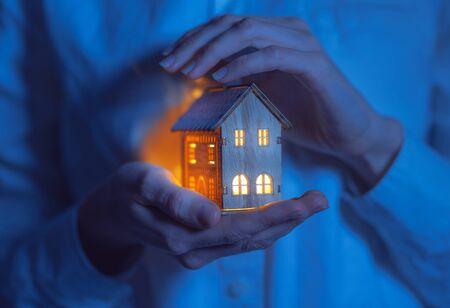 concept technologie protection de la maison contre le froid. maison dans des mains féminines attentionnées