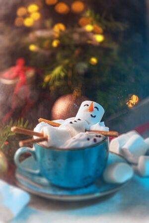 Christmas background with a marshmallow man lying in a mug with cocoa, in the background a Christmas tree with toys, a garland and gifts