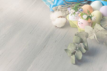 Easter concept. Easter eggs painted in pastel colors with cute faces in an egg tray with wreaths put on them. Light background, place for text.