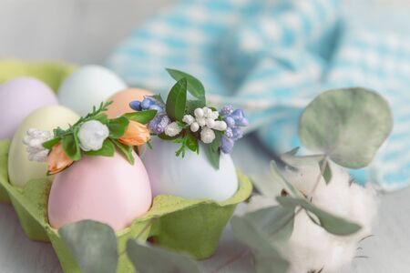Easter concept. Easter eggs painted in pastel colors in an egg tray with wreaths on them. Light background, place for text.