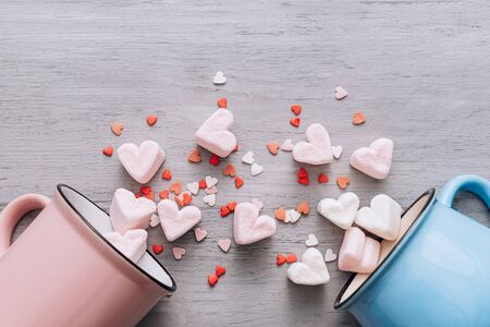 two mugs of blue and pink lie on their side, small candy hearts and marshmallow hearts spilled out 스톡 콘텐츠