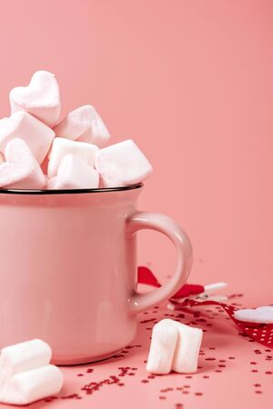 pink mug on a pink background filled with marshmallows in the form of hearts. valentine's day holiday concept