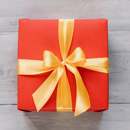 red gift box tied with a golden ribbon. Ribbon tied with a bow on a box. gift concept
