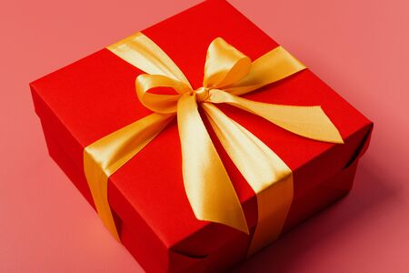red box tied with a gold ribbon. the ribbon is tied on a box in the form of a beautiful bow. holiday gift concept 스톡 콘텐츠