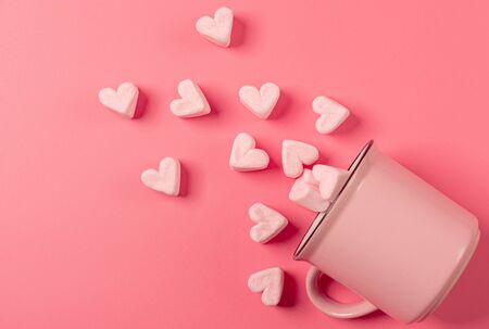 a pink mug lies on its side against a pink background, light-pink marshmallows sprinkled from it in the form of hearts