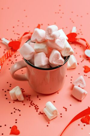 pink mug on a pink background filled with marshmallows in the form of hearts. next to it is a box with a gift for Valentine's Day. valentine's day holiday concept