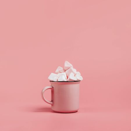 pink mug on a pink background filled with marshmallows in the form of hearts. next to it is a box with a gift for Valentines Day. valentines day holiday concept