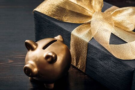 a gift wrapped in black paper and tied with a gold ribbon next to it stands a golden piggy piggy bank
