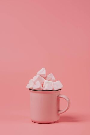 pink mug on a pink background filled with marshmallows in the form of hearts. valentines day holiday concept
