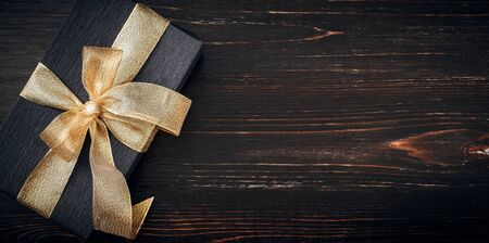 a gift wrapped in black paper and tied with a gold ribbon. expensive gift concept.