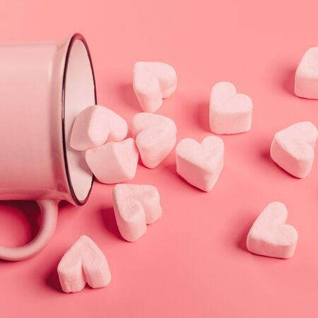a pink mug lies on its side against a pink background, light-pink marshmallows sprinkled from it in the form of hearts 스톡 콘텐츠