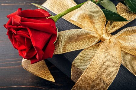 Gift wrapped in black paper and a gold ribbon. on top of the box is a luxurious red rose. The concept of an expensive gift for the holiday Valentines Day or Womens Day March 8