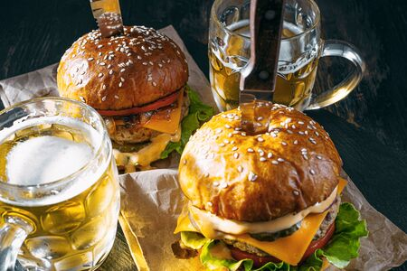 two delicious beef burger on a wooden table near two glass of cold beer Standard-Bild