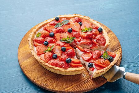 quiche with lime zest and strawberry slices with blueberries and fresh mint leaves on a blue wooden table. one slice is cut out of the pie and it is ready to serve. Standard-Bild