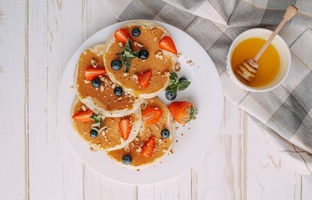 Pancake breakfast concept with honey and nuts berries.