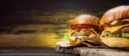 two tasty beef burger on a wooden table