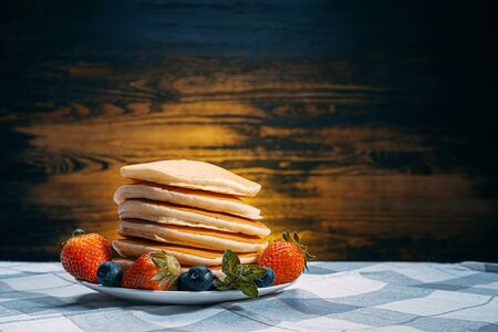 classic homemade pancakes with berries on a white saucer on a dark wooden background in a rustic style. Standard-Bild