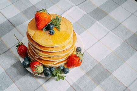 on classic homemade pancakes with berries on a white saucer on a light wooden background in a rustic style
