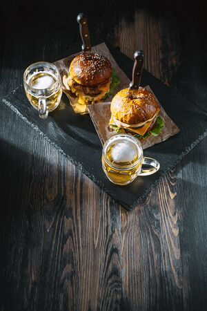 two delicious beef burger on a wooden table near two glass of cold beer Фото со стока