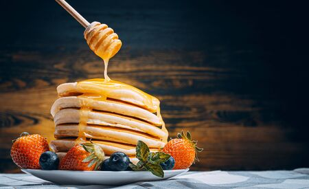 on classic homemade pancakes with berries on a white saucer on a dark wooden background in a rustic style pours delicious honey. Фото со стока