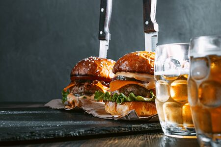 two delicious beef burger on a wooden table near two glass of cold beer Standard-Bild - 147256085